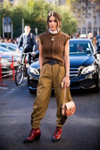 PARIS, FRANCE - SEPTEMBER 27:  Camila Coelho, wearing a sleeveless brown sweater, tan pants, red boots and Chloe bag, is seen after the Chloe show on September 27, 2018 in Paris, France. (Photo by Claudio Lavenia/Getty Images)