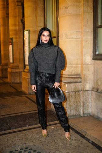 PARIS, FRANCE - OCTOBER 01: Fiona Zanetti wears long bejeweled earrings, a gray turtleneck oversized wool pullover with puff sleeves, black leather pants, a black leather Coperni bag, golden shiny pointy shoes, outside Isabel Marant, during Paris Fashion Week - Womenswear Spring Summer 2021, on October 01, 2020 in Paris, France. (Photo by Edward Berthelot/Getty Images)