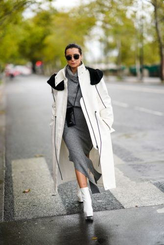 PARIS, FRANCE - OCTOBER 06: Julia Comil wears sunglasses, a white log coat with black shoulder pads, a gray wool turtleneck dress, a black leather small bag, white shoes, outside Louis Vuitton, during Paris Fashion Week - Womenswear Spring Summer 2021, on October 06, 2020 in Paris, France. (Photo by Edward Berthelot/Getty Images)