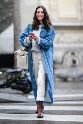 PARIS, FRANCE - FEBRUARY 28:  A guest wears a blue denim long jacket, brown boots, a white top, and white pants outside the JOUR/NE show, during Paris Fashion Week Womenswear Fall/Winter 2017/2018, on February 28, 2017 in Paris, France.  (Photo by Edward Berthelot/Getty Images)