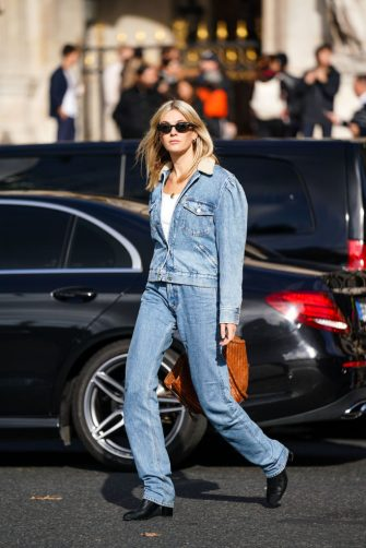 PARIS, FRANCE - SEPTEMBER 30: Camille Charrière wears earrings, sunglasses, a white top, a washed-out light blue denim jacket with a cream-color fluffy collar, washed out light blue denim full-length pants, black boots, a brown large bag, outside Stella McCartney , during Paris Fashion Week - Womenswear Spring Summer 2020, on September 30, 2019 in Paris, France. (Photo by Edward Berthelot/Getty Images)