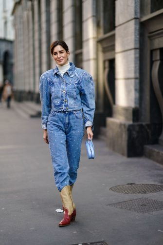 MILAN, ITALY - FEBRUARY 22: Gala Gonzalez wears a blue denim jacket with shoulder pads, a white turtleneck pullover, blue denim pants, cowboy boots, a bag, outside Philosophy, during Milan Fashion Week Fall/Winter 2020-2021 on February 22, 2020 in Milan, Italy. (Photo by Edward Berthelot/Getty Images)