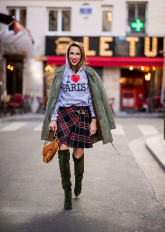 PARIS, FRANCE - SEPTEMBER 25: Alexandra Lapp is seen wearing a plaid kilt skirt from maje, an I love Paris sweatshirt from a souvenir shop in Paris, a green parka jacket with teddy fur from Steffen Schraut, the Dior saddle bag made of calfskin in cognac and the Era Suede 110 over knee boot in green velvet from Saint Laurent during Paris Fashion Week Womenswear Spring/Summer 2019 on September 25, 2018 in Paris, France. (Photo by Christian Vierig/Getty Images)