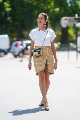 PARIS, FRANCE - JULY 02: Helena Bordon wears long earrings, a white t-shirt, a golden skirt, shoes, a golden Chanel bag, outside Chanel, during Paris Fashion Week -Haute Couture Fall/Winter 2019/2020, on July 02, 2019 in Paris, France. (Photo by Edward Berthelot/Getty Images)