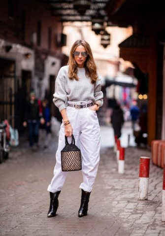 MARRAKECH, MOROCCO - NOVEMBER 25: Alexandra Lapp is seen wearing an oversized grey wool sweater from H&M, white high-rise boyfriend style jeans from Isabel Marant Etoile, a black leather belt with white stitches from Isabel Marant, black Cowboy boots with a silver tip from Isabel Marant, a handwoven basket bag from Sensistudio and mirrored sunglasses from Givenchy on November 25, 2018 in Marrakech, Morocco. (Photo by Christian Vierig/Getty Images)