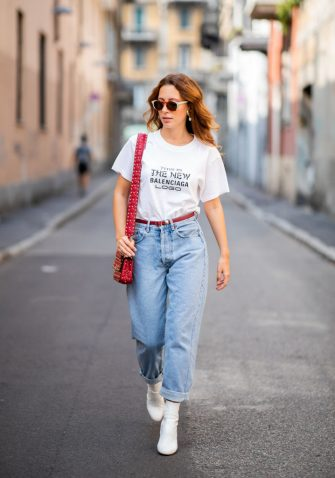 MILAN, ITALY - SEPTEMBER 19: A guest wearing white Balenciaga tshirt, cuffed denim boyfriends jeans, white ankle boots, red Valentino bag, sunglasses during Milan Fashion Week Spring/Summer 2019 on September 19, 2018 in Milan, Italy. (Photo by Christian Vierig/Getty Images)