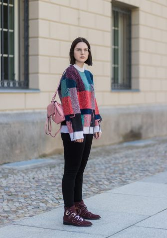 BERLIN, GERMANY - AUGUST 17: Maria Barteczko wearing patchwork oversized wool sweater Stella McCartney, black skinny jeans Madewell, red buckle boots with studs Givenchy, silver knot bracelet Celine, mini Faye backpack in light rose Chloe, round gold glasses Ray Ban on August 17, 2017 in Berlin, Germany. (Photo by Christian Vierig/Getty Images)