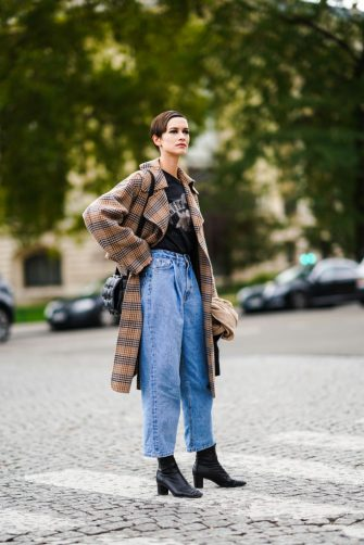 PARIS, FRANCE - OCTOBER 06: A model wears t-shirt, a brown checked trench coat, a black woven leather Bottega Veneta bag, blue denim jeans, black leather boots, outside Chanel, during Paris Fashion Week - Womenswear Spring Summer 2021, on October 06, 2020 in Paris, France. (Photo by Edward Berthelot/Getty Images)