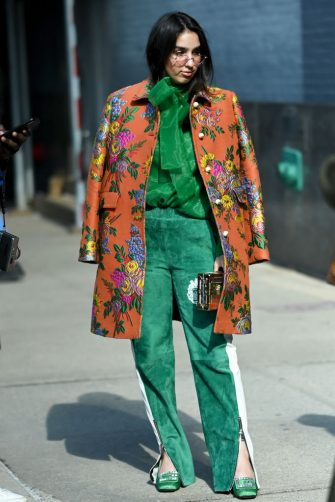 NEW YORK, NEW YORK - FEBRUARY 09: A guest wears track-suit inspired green suede trousers with an emerald-green blouse and a floral brocade waist-length coat outside of Spring Studios during New York Fashion Week Fall/Winter '20 on February 09, 2020 in New York City. (Photo by Shannon Finney/Getty Images)