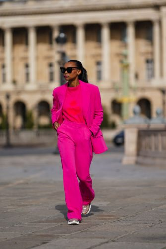 PARIS, FRANCE - FEBRUARY 25: Emilie Joseph wears sunglasses, a neon pink oversized blazer jacket from Zara, a neon pink pullover from Isabel Marant, flared pants, bronze colored shiny sneakers shoes from Valentino, on February 25, 2021 in Paris, France. (Photo by Edward Berthelot/Getty Images)