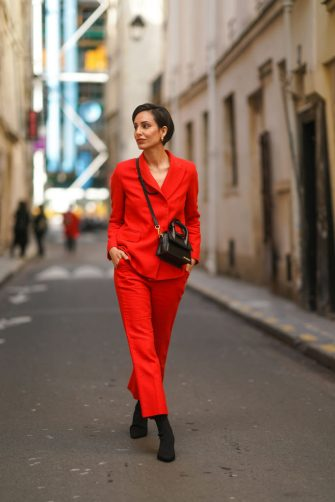 PARIS, FRANCE - FEBRUARY 23: Adriana Seminario wears a red blazer jacket from Sandro, red suit pants from Sandro, a black leather Jacquemus bag, black kitten heels suede pointy shoes, on February 23, 2021 in Paris, France. (Photo by Edward Berthelot/Getty Images)