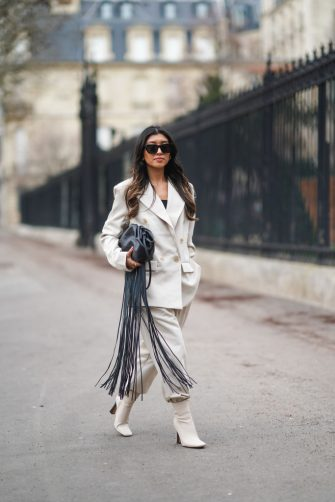 PARIS, FRANCE - FEBRUARY 16: Angela Gonzalez wears sunglasses, a black top, a white oversized blazer jacket, a black leather bag with long fringes, white suit pants, white high heels pointy ankle boots, on February 16, 2021 in Paris, France. (Photo by Edward Berthelot/Getty Images)