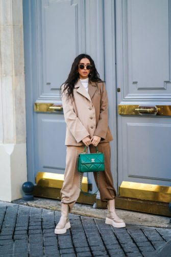 PARIS, FRANCE - DECEMBER 15: Gabriella Berdugo wears  sunglasses, a white turtleneck pullover, earrings, a necklace, a bi color beige and brown oversized blazer jacket and suit pants from Salisa NYC, beige nude biker platform shiny boots, a green quilted leather Chanel bag, on December 15, 2020 in Paris, France. (Photo by Edward Berthelot/Getty Images)