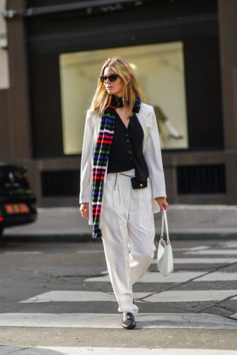 PARIS, FRANCE - MARCH 02: Natalia Verza aka Mascarada wears sunglasses, earrings, a long colored striped scarf, a black vest, a white oversized blazer jacket, a small Chanel belt bag, white suit pants, a white Cleo Prada bag, black Chanel loafers shoes, on March 02, 2021 in Paris, France. (Photo by Edward Berthelot/Getty Images)