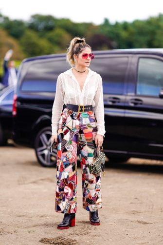 PARIS, FRANCE - SEPTEMBER 24:  Thassia Naves wears a white lace mesh shirt, patchwork multicolor printed pants, black leather boots with red heels, a Dior Saddle bag, pink sunglasses, outside Dior, during Paris Fashion Week Womenswear Spring/Summer 2019, on September 24, 2018 in Paris, France.(Photo by Edward Berthelot/Getty Images)