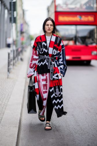 BERLIN, GERMANY - JULY 13: Maria Barteczko is seen wearing a patchwork knit coat Stella McCartney, black skinny jeans Acne Studios, black studded sandals Givenchy, black logo shopping tote bag Balenciaga, retro glasses Ray Ban on July 13, 2018 in Berlin, Germany. (Photo by Christian Vierig/Getty Images)