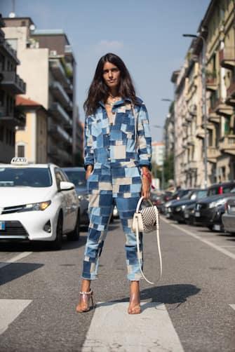 MILAN, ITALY - SEPTEMBER 21: Chiara Totire at Etro in a blue  denim patchwork jumpsuit, white purse, clear heels  during Milan Fashion Week Spring/Summer 2019 on September 21, 2018 in Milan, Italy.