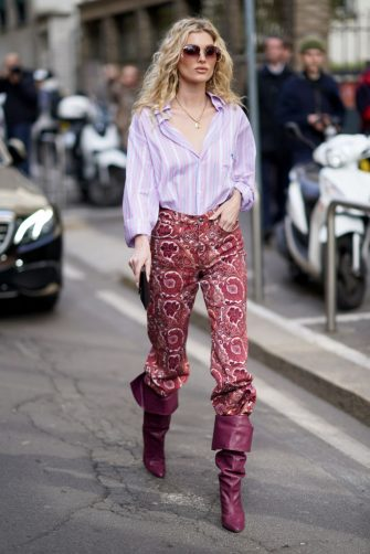 MILAN, ITALY - FEBRUARY 21: Romee Strijd wears a mauve pale purple shirt, a golden necklace, red pants with floral print, purple leather pointy boots, outside Etro, during Milan Fashion Week Fall/Winter 2020-2021 on February 21, 2020 in Milan, Italy. (Photo by Edward Berthelot/Getty Images)