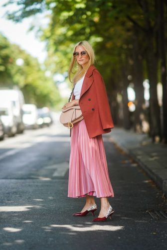 PARIS, FRANCE - JULY 01: Charlotte Groeneveld wears, outside Dior, sunglasses,a white top, a Dior bag, a light rust-color jacket, a lustrous pink pleated skirt, shiny Dior pointy heeled pumps, during Paris Fashion Week -Haute Couture Fall/Winter 2019/2020, on July 01, 2019 in Paris, France. (Photo by Edward Berthelot/Getty Images)