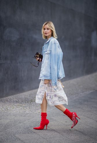 BERLIN, GERMANY - JULY 06: Lisa Hahnbueck wearing Zimmermann dress, a denim jeans jacket Off White, red vintage Chanel belt bag, red Balenciaga x Colette Knife boots during the Mercedes-Benz Fashion Week Berlin Spring/Summer 2018 on July 6, 2017 in Berlin, Germany. (Photo by Christian Vierig/Getty Images)