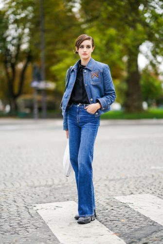 PARIS, FRANCE - OCTOBER 06: A model wears a blue denim Prada jacket, a black shirt, blue flared jeans, shoes, outside Chanel, during Paris Fashion Week - Womenswear Spring Summer 2021, on October 06, 2020 in Paris, France. (Photo by Edward Berthelot/Getty Images)