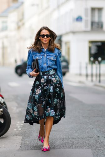 PARIS, FRANCE - OCTOBER 08: Therese Hellström wears sunglasses, a blue denim jacket from Custommade, a studded black leather clutch from Valentino, a black pleated floral print mesh skirt from Custommade, pink pointy Custommade shoes, on October 08, 2020 in Paris, France. (Photo by Edward Berthelot/Getty Images)