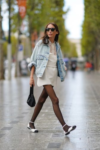 PARIS, FRANCE - OCTOBER 06: A guest wears sunglasses, a pale blue denim jacket, a white dress, a black Prada bag, black tights, white flat shoes with black tip, outside Miu Miu, during Paris Fashion Week - Womenswear Spring Summer 2021, on October 06, 2020 in Paris, France. (Photo by Edward Berthelot/Getty Images)