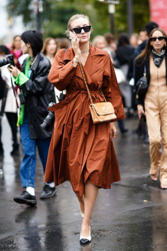 PARIS, FRANCE - OCTOBER 01: A guest wears sunglasses, a brown dress, a bag from Chanel, Chanel shoes, outside Chanel, during Paris Fashion Week - Womenswear Spring Summer 2020, on October 01, 2019 in Paris, France. (Photo by Edward Berthelot/Getty Images)