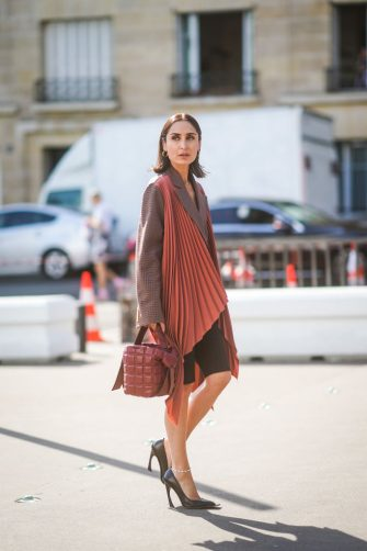 PARIS, FRANCE - JUNE 30: Geraldine Boublil wears earrings  a brown checkered oversized jacket with rust-color pleated panels, black cycling shorts, a brown quilted Acne Studios bag, an anklet, black pointy heeled pumps, outside Acne, during Paris Fashion Week - Haute Couture Fall/Winter 2019/2020, on June 30, 2019 in Paris, France. (Photo by Edward Berthelot/Getty Images)