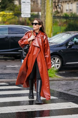 PARIS, FRANCE - MARCH 02: Chloe Harrouche wears sunglasses, earrings, a Bottega Veneta bag with a golden chain handle, a red leather trench long coat, black pants, black boots, outside Akris, during Paris Fashion Week - Womenswear Fall/Winter 2020/2021, on March 02, 2020 in Paris, France. (Photo by Edward Berthelot/Getty Images)