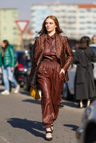 MILAN, ITALY - FEBRUARY 22: Larsen Thompson wears a dark brown leather shirt, dark brown leather baggy pants with an elasticated waist, a rust-color and dark brown python pattern jacket, black pointy strappy shoes, a yellow handbag, outside MSGM, during Milan Fashion Week Fall/Winter 2020-2021 on February 22, 2020 in Milan, Italy. (Photo by Edward Berthelot/Getty Images)