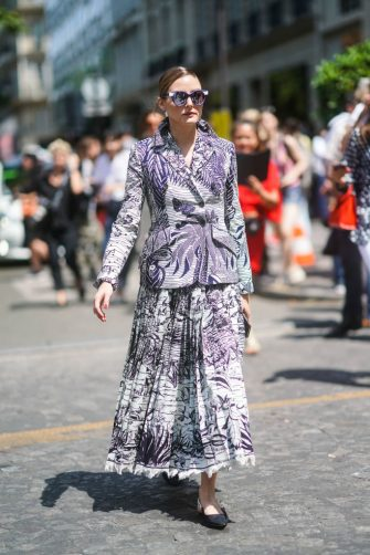PARIS, FRANCE - JULY 01: Olivia Palermo wears mirrored sunglasses, a white and black landscape pattern Dior jacket, an assorted fringed long pleated skirt, black Dior J'Adior shoes, outside Dior, during Paris Fashion Week -Haute Couture Fall/Winter 2019/2020, on July 01, 2019 in Paris, France. (Photo by Edward Berthelot/Getty Images)