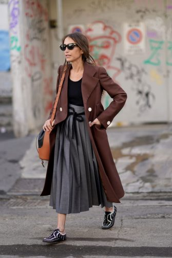 MILAN, ITALY - FEBRUARY 21: Chloe Harrouche wears sunglasses, a brown long jacket, a black top, a gray pleated skirt, a leather brown and black Loewe bag, black and white shoes, outside Marni, during Milan Fashion Week Fall/Winter 2020-2021 on February 21, 2020 in Milan, Italy. (Photo by Edward Berthelot/Getty Images)