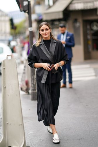 PARIS, FRANCE - SEPTEMBER 29: Olivia Palermo wears a black jacket, a black pleated skirt, white shoes, outside Ralph & Russo, during Paris Fashion Week - Womenswear Spring Summer 2020, on September 29, 2019 in Paris, France. (Photo by Edward Berthelot/Getty Images)