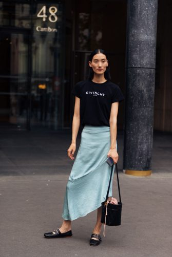 PARIS, FRANCE - JULY 01: Model Lina Zhang wears a black Givenchy Paris shirt, teal asymmetrical silk skirt, black Givenchy bucket bag, and black Miu Miu ballerina flats after the Schiaparelli show during Couture Fashion Week Fall/Winter 2019 on July 01, 2019 in Paris, France. (Photo by Melodie Jeng/Getty Images)
