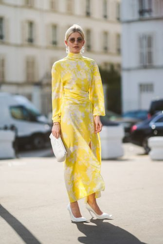 PARIS, FRANCE - JUNE 30: Caroline Daur wears earrings, sunglasses, a yellow and white dress, a white bag, white shoes, outside Acne, during Paris Fashion Week - Haute Couture Fall/Winter 2019/2020, on June 30, 2019 in Paris, France. (Photo by Edward Berthelot/Getty Images)