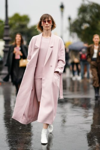PARIS, FRANCE - OCTOBER 01: Anya Ziourova wears sunglasses, a pink long coat, a pink top, a pink skirt, white shoes, outside Chanel, during Paris Fashion Week - Womenswear Spring Summer 2020, on October 01, 2019 in Paris, France. (Photo by Edward Berthelot/Getty Images)