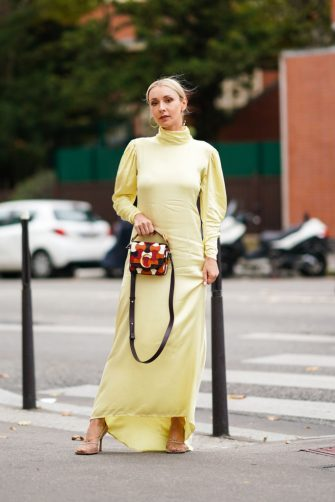 PARIS, FRANCE - SEPTEMBER 26: Justyna Czerniak wears earrings, a light yellow hi-neck puff sleeves asymmetric long dress, a Chloe orange, brown and white bag, mesh heels, outside Ann Demeulemeester, during Paris Fashion Week - Womenswear Spring Summer 2020 on September 26, 2019 in Paris, France. (Photo by Edward Berthelot/Getty Images)