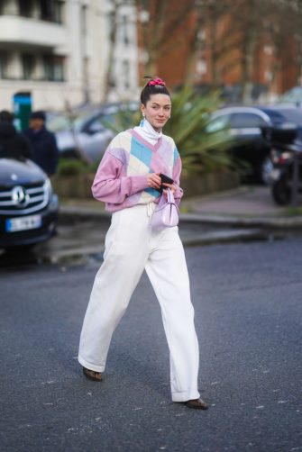 PARIS, FRANCE - MARCH 03: A guest wears a white turtleneck pullover, a pink argyle pattern printed wool pullover, white pants, a purple leather bag, pointy shoes, earrings, outside Lacoste, during Paris Fashion Week - Womenswear Fall/Winter 2020/2021 on March 03, 2020 in Paris, France. (Photo by Edward Berthelot/Getty Images)
