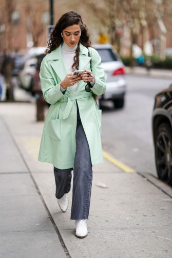 NEW YORK, NEW YORK - FEBRUARY 12: A guest wears a pale green trench coat, a white turtleneck pullover, gray jeans, white shoes, during New York Fashion Week Fall Winter 2020, on February 12, 2020 in New York City. (Photo by Edward Berthelot/Getty Images)