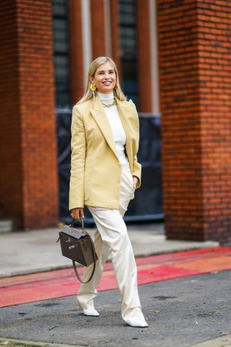 PARIS, FRANCE - OCTOBER 03: Xenia Adonts wears golden earrings, a white turtleneck pullover, a pale yellow oversized blazer jacket, a brown Hermes bag, a golden chain necklace, white flared silky lustrous pants, white leather pointy shoes, outside Hermes, during Paris Fashion Week - Womenswear Spring Summer 2021 on October 03, 2020 in Paris, France. (Photo by Edward Berthelot/Getty Images)