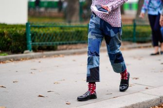 PARIS, FRANCE - SEPTEMBER 27:  A guest wears denim shades of blue patchwork pants, red print socks, black moccasins, outside Lanvin, during Paris Fashion Week Womenswear Spring/Summer 2018, on September 27, 2017 in Paris, France.  (Photo by Edward Berthelot/Getty Images)