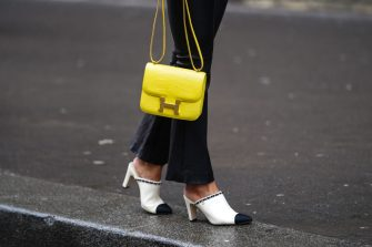PARIS, FRANCE - MARCH 02: A guest wears a yellow Hermes crocodile pattern bag and Chanel shoes, outside Giambattista Valli, during Paris Fashion Week - Womenswear Fall/Winter 2020/2021, on March 02, 2020 in Paris, France. (Photo by Edward Berthelot/Getty Images)