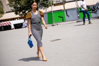 PARIS, FRANCE - JUNE 23: A guest, wearing an orange, white and black checked dress, orange sandals and blue Kenzo bag, is seen outside Kenzo fashion show on Day 6 during the Paris Fashion Week Spring/Summer 202> on June 23, 2019 in Paris, France. (Photo by Claudio Lavenia/Getty Images)