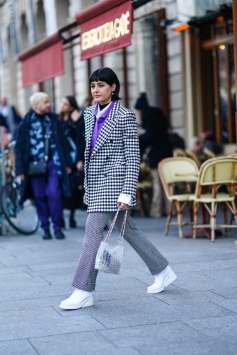 PARIS, FRANCE - JANUARY 22: Maria Bernad wears earrings, a black and white checked oversized jacket, a white shirt, a purple shirt, white shoes, a bag made of clear plastic parts, outside Viktor & Rolf, during Paris Fashion Week - Haute Couture Spring/Summer 2020, on January 22, 2020 in Paris, France. (Photo by Edward Berthelot/Getty Images )