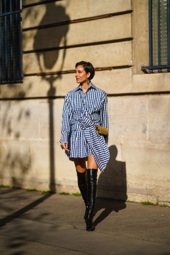PARIS, FRANCE - FEBRUARY 23: Adriana Seminario wears earrings, a blue and white checked pattern printed dress from Marques Almeida, a golden metallic Saint-Laurent YSL bag, thigh high leather black pointy boots from Mi/Mai, on February 23, 2021 in Paris, France. (Photo by Edward Berthelot/Getty Images)
