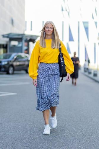 COPENHAGEN, DENMARK - AUGUST 09: A guest wearing yellow sweater, grey plaid skirt, sneakers on August 09, 2017 in Copenhagen, Denmark. (Photo by Christian Vierig/Getty Images)