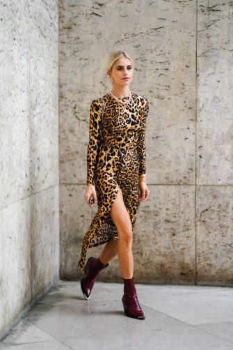 PARIS, FRANCE - SEPTEMBER 26: Caroline Daur wears a black and yellow tiger print dress, burgundy boots, earrings, outside Paco Rabanne, during Paris Fashion Week - Womenswear Spring Summer 2020 on September 26, 2019 in Paris, France. (Photo by Edward Berthelot/Getty Images)