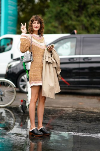 PARIS, FRANCE - OCTOBER 01: A guest wears a brown wool dress with printed patterns, a silver quilted Chanel bag, black leather shoes, holds a trench coat, outside Chanel, during Paris Fashion Week - Womenswear Spring Summer 2020, on October 01, 2019 in Paris, France. (Photo by Edward Berthelot/Getty Images)