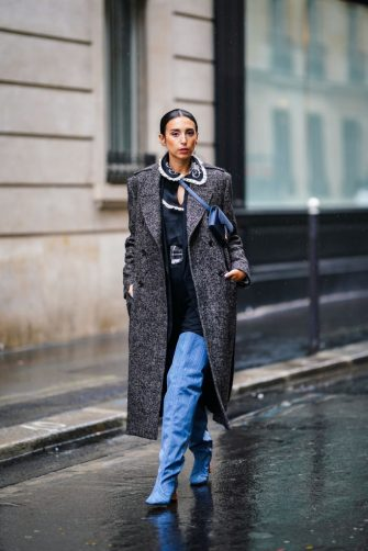 PARIS, FRANCE - OCTOBER 05: Gabriella Berdugo wears a gray long wool coat, a blue Dior small bag, a black dress with white ruffled collar and floral embroidery, blue pointy high heeled thigh high boots, outside Paul & Joe, during Paris Fashion Week - Womenswear Spring Summer 2021 on October 05, 2020 in Paris, France. (Photo by Edward Berthelot/Getty Images)